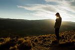 Andean Mountain Cat (Leopardus jacobita) biologist, Juan Reppucci, talking on cell phone at sunset, Abra Granada, Andes, northwestern Argentina