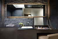 A modern grey bathroom with a textured slate and a tiled wall. A mirror hangs on the wall above a washbasin set in a cupboard unit, which has a built-in dressing table area. Concealed lighting is placed behind the mirror.