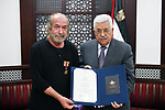 Palestinian President Mahmoud Abbas honors of artist Taleb Dweik, in the West Bank city of Ramallah, on August 15, 2017. Photo by Thaer Ganaim