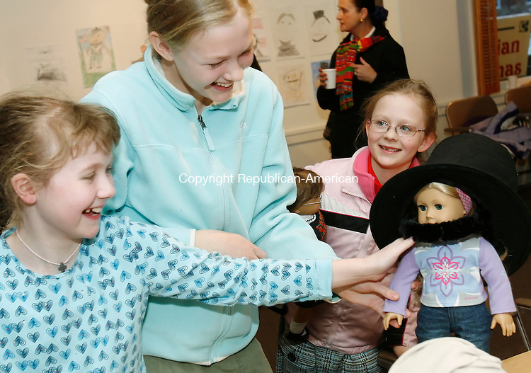 TORRINGTON, CT 02/12/09- 021209BZ02- From left- RachelInman,10, Ellie Uzarski, 12, and Molly Uzarski, 8, laugh while dressing Ellie's American Girl doll &quot;Elizabeth&quot; in President Abraham Lincoln's signature stovepipe hat and beard during a 200th &quot;birthday party&quot; for the President at the Torrington Historical Society Thursday afternoon. <br /> Jamison C. Bazinet Republican-American