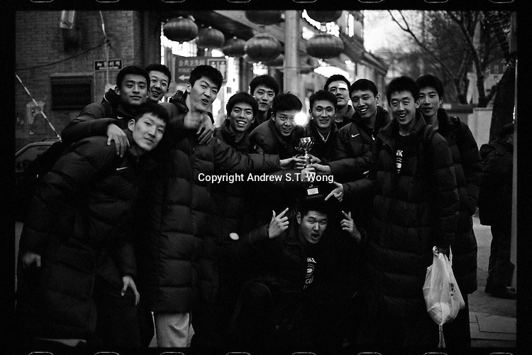Players of Tsinghua University Affiliated Middle School basketball team display the champion trophy after winning a high school basketball tournament in Beijing, January 2012.