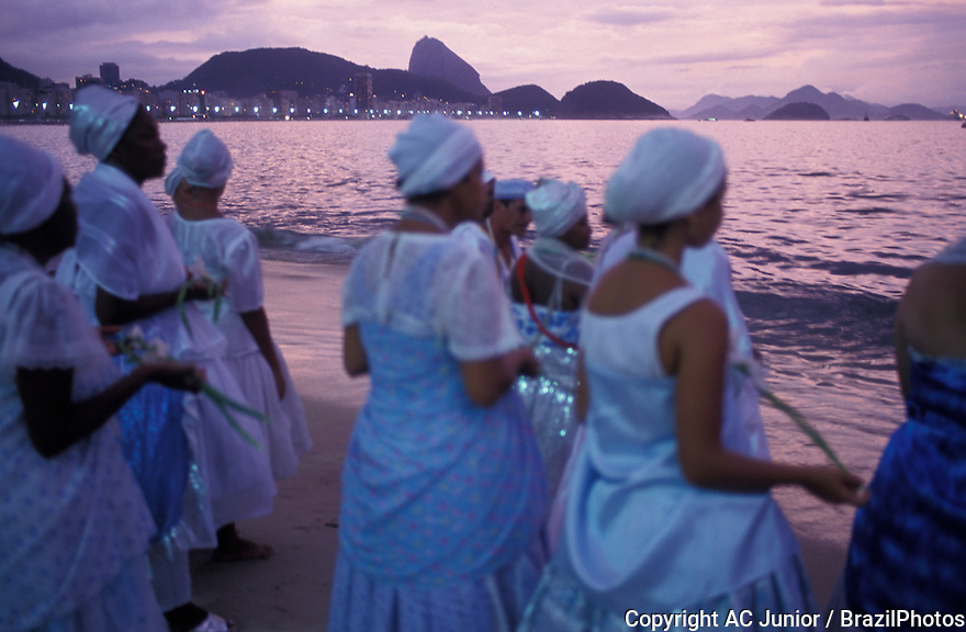 Offerings to Iemanja, the Sea Queen, Rio de Janeiro, Brazil. New Year celebration at Copacabana beach. Afro-brazilian women ( baianas from Umbanda religious rituals ) releasing palm flowers into the ocean.