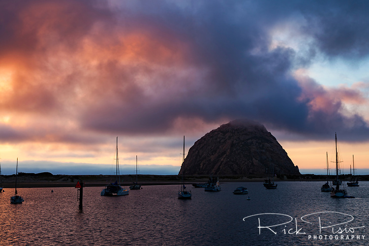 Fog sits at the peak of Morro Rock as the sun sets behind the Morro Bay Harbor along the California coast.