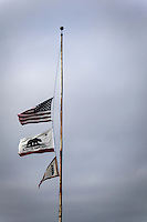 The United States,  California State  and  Lighthouse Service flags fly at half mast, or half staff against a gray, overcast sky.