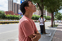 People wait at a bus stop in Xian, Shaanxi Province, China.