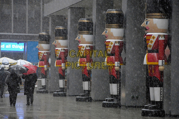 SNOW FALLING .Pedestrians walk past giant nutcrackers in front of UBS on Sixth Avenue as snow falls late Thursday morning in New York City, New York, USA,.12 December 2007..umbrella people pedestrian snowing.CAP/ADM/BL.©Bill Lyons/AdMedia/Capital Pictures. *** Local Caption ***