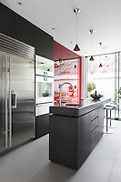 A set of ruby pendant lights by Baccarat inspired the colour scheme for this contemporary kitchen