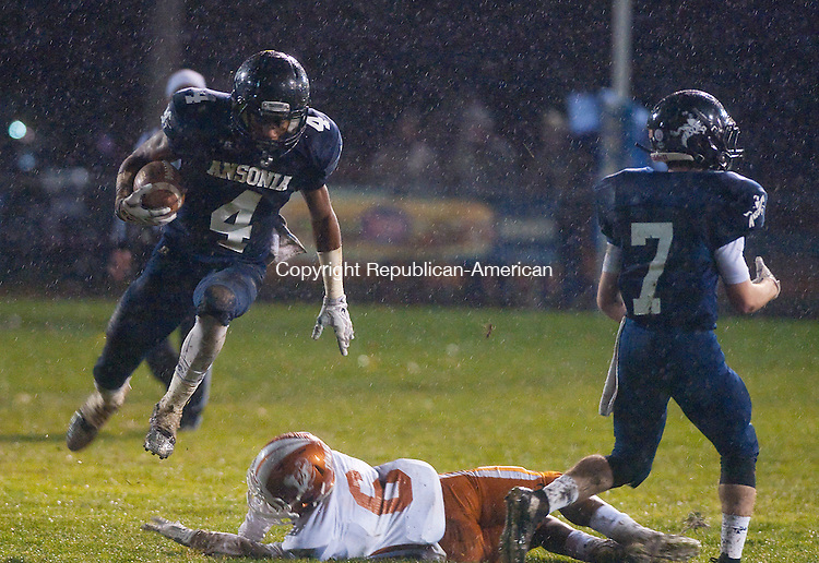 ANSONIA, CT--- -120115JS09--Ansonia's Tajik Bagley (4) jumps over a tackle attempt by Capital Prep's Rich Hunter (6) during their Class S Quarterfinal game Tuesday at Jarvis Stadium in Ansonia. <br /> Jim Shannon Republican-American