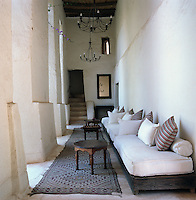 A long banquette filled with plump cushions lines a corridor which runs along the courtyard garden