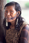 Pikany Village, Brazil. Kayapo Indian woman with black body paint and wearing earrings.