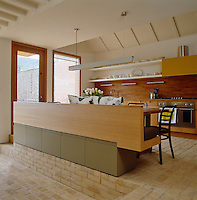 The raised open-plan kitchen/dining area has a bespoke wooden table and bench and wooden splashback that runs the length of the wall