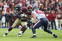 Landover, MD - November 18, 2018: Washington Redskins running back Adrian Peterson (26) is tackled by Houston Texans outside linebacker Jadeveon Clowney (90) during the  game between Houston Texans and Washington Redskins at FedEx Field in Landover, MD.   (Photo by Elliott Brown/Media Images International)