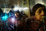 Aude Back de Surany, center, and other passengers are reflected in the back window of an uptown C train traveling through a subway tunnel in New York, New York on January 30, 2015.