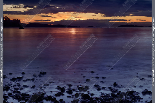 Dramatic sunset sky and ocean shore pebbles over the Strait of Georgia, Salish Sea, Pacific Ocean in Nanaimo, Vancouver Island, BC, Canada