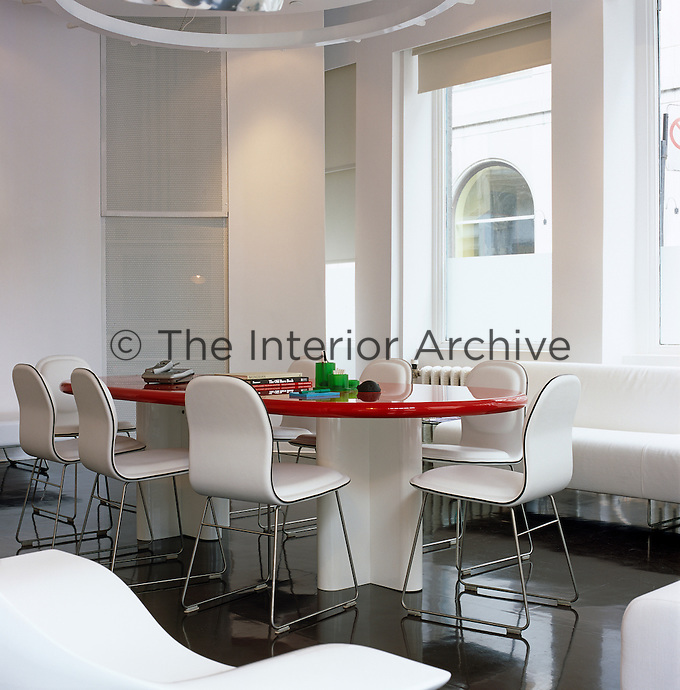 White chairs and furnishings with a pill-shaped red table designed by Denis Blais are offset by the black lacquer floor of this contemporary home office