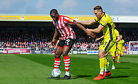 Lincoln City's John Akinde shields the ball from Cheltenham Town's Chris Hussey<br /> <br /> Photographer Chris Vaughan/CameraSport<br /> <br /> The EFL Sky Bet League Two - Lincoln City v Cheltenham Town - Saturday 13th April 2019 - Sincil Bank - Lincoln<br /> <br /> World Copyright &copy; 2019 CameraSport. All rights reserved. 43 Linden Ave. Countesthorpe. Leicester. England. LE8 5PG - Tel: +44 (0) 116 277 4147 - admin@camerasport.com - www.camerasport.com