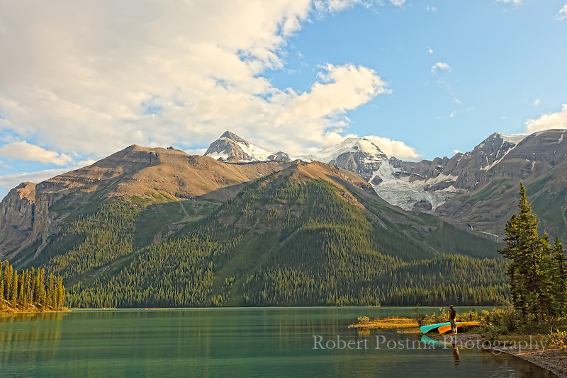 A person stands on the shores of Maligne Lake during late afternoon sunlight.