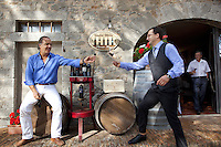 Italy. Tuscany. Villa A Sesta is part of the village Castelnuovo. Riccardo Tattoni is seated on a wooden barrel at the entrance of the wine shop and cellar from Agricola Tattoni Villa A Sesta. He is sampling red wine with some friends. 18.09.10 © 2010 Didier Ruef