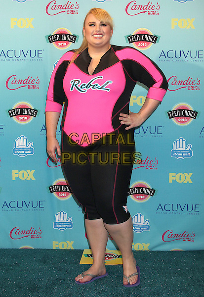 Rebel Wilson<br /> 2013 Teen Choice Awards - Press Room held at Gibson Amphitheatre, Universal City, California, USA.<br /> August 11th, 2013<br /> full length hand on hip pink black name words writing wetsuit drysuit flip flops <br /> CAP/ADM/RE<br /> &copy;Russ Elliot/AdMedia/Capital Pictures