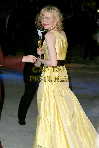 CATE BLANCHETT.2005 Vanity Fair Oscar Party held at Morton's Restaurant. West Hollywood, CA.February 27th, 2005.Photo Credit: Jacqui Wong/AdMedia.full length award trophy yellow silk satin one shoulder dress looking over shoulder.www.capitalpictures.com.sales@capitalpictures.com.© Capital Pictures.