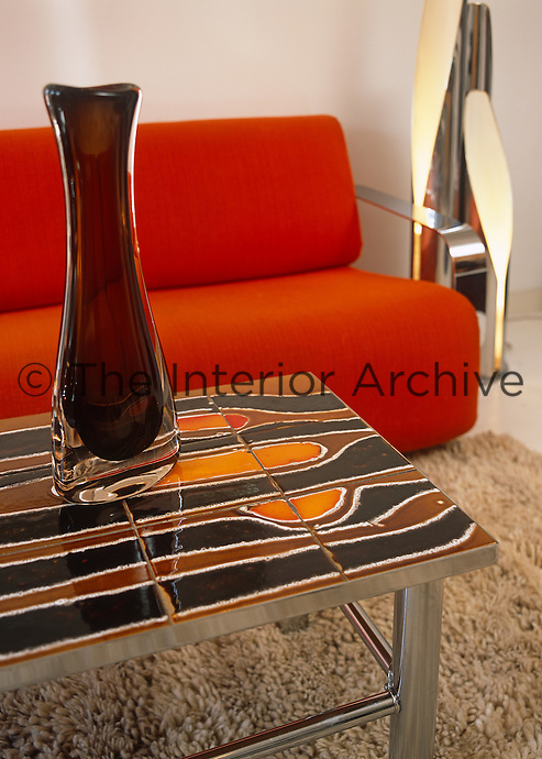 A brown glass vase on a tile-topped table with an orange sofa in this 1970's themed sitting room