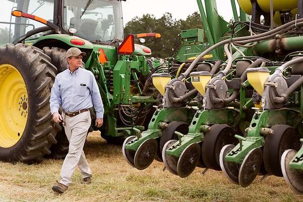 April 20, 2016. Rowland, North Carolina. <br />  Bo Stone walks away from his tractor and planter before it begins to plant corn on a field a mile or so from his home. The machines are satellite guided and cost nearly $500,000.<br />  Bo Stone, age 44, runs a 2300 acre farm near the South Carolina border. After 5 generations of tobacco farming, Stone helped to move his family farm over to corn, wheat, soybeans, and strawberries 7 years ago. <br />  While his corn crop is entirely made up of stacked genetically modified strains of corn, Stone says he chose the varieties primarily for their yield characteristics, but having the ability to utilize their herbicide tolerant traits if a weed gets out of control is &quot;another tool in my toolbox&quot;.