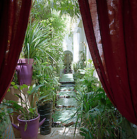 Linen curtains frame a doorway which opens onto a narrow path punctuated with star-shaped stepping stones and lined with plants