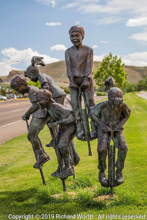 """New Heights"" is a scuplture of  happy children bouncing on pogo sticks.  The creation of artist Gary Lee Price, this installation resides in front of a senior center in Green River, Wyoming."