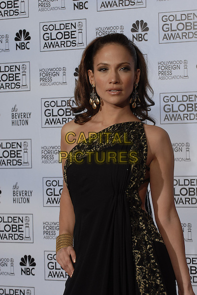 "JENNIFER LOPEZ.Pressroom - 64th Annual Golden Globe Awards, Beverly Hills HIlton, Beverly Hills, California, USA..January 15th 2007. .globes press room Marchesa half one shoulder gold pattern black earrings dress straps bracelet hand on hip.CAP/AW.Please use accompanying story.Supplied by Capital Pictures.© HFPA"" and ""64th Golden Globe Awards"""