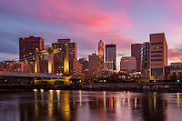 Colorful sunset over Minneapolis skyline with the Mississippi River and Hennepin Avenue bridge in the foreground. The Mississippi River through the Twin Cities is part of the Mississippi National River & Recreation Area.