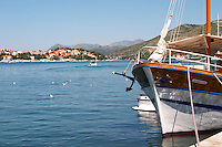 Pleasure boats moored on buoys and along the key, villas along the coast. Mountains mountain tops in the background. In the foreground the stern front of a wooden schooner sailing ship called Marijana. Luka Gruz harbour. Dubrovnik, new city. Dalmatian Coast, Croatia, Europe.
