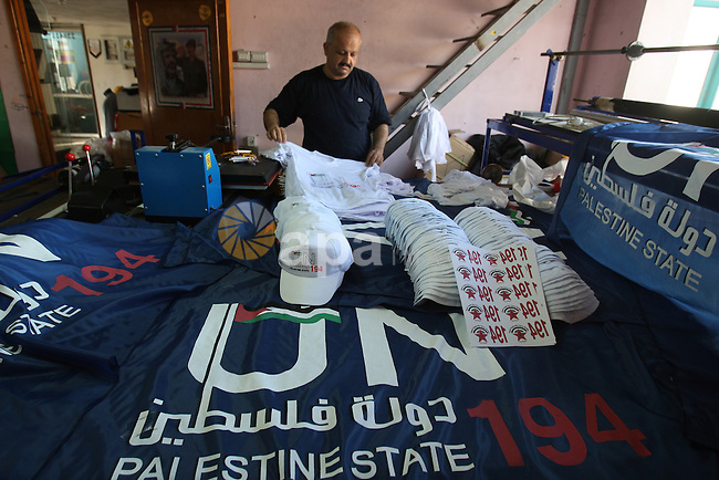 Palestinian man folds t-shirts bearing a symbolic emblem of a proposed future Palestinian state at a work shop in the West Bank city of Nablus .Saturday,Sept. 17, 2011. Palestinian President Mahmoud Abbas is set to address the U.N. next week, planning to ask the world to recognize a Palestinian state. Number 194 represents the Palestinian hope to become 194th member of the UN . Photo by Wagdi Eshtayah