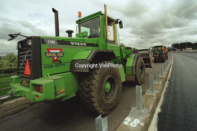 Foto: VidiPhoto..RENKUM - De machines van wegenbouwer Bruil uit Ede en van loonwerker Gerritsen uit Heelsum komen elkaar tegen op het fietspad van de Rijnbrug (A50) bij Renkum. Elkaar passeren is onmogelijk. Gerritsen moet naar boeren in de Betuwe en omrijden via Arnhem kost hem enorm veel tijd en geld. Daarom mag hij gebruik maken van het fietspad. Omdat er op dit moment een zesde rijstrook op de Rijnbrug wordt aangelegd, maakt ook Bruil gebruik van het fietspad. En dat zorgt nog wel eens voor irritaties, want een moet er altijd terug.