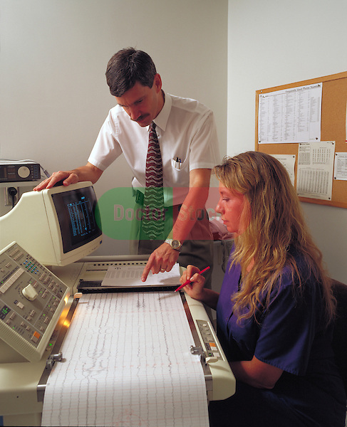 doctor or technicians reviewing digital EEG printout