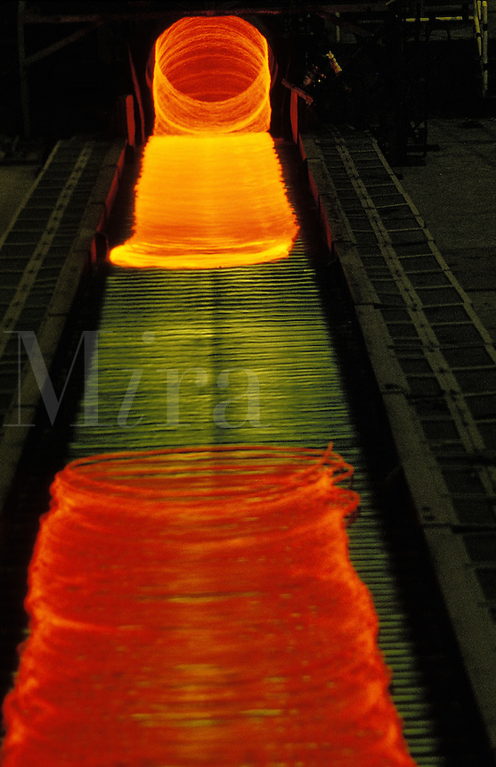 Red hot steel wire coil cooling at the exit of hot wire mill. Iron and steel industry.