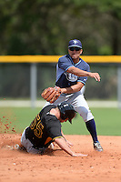 Tampa Bay Rays second baseman Kean Wong (7) turns a double play as Michael Suchy (55) slides in during an Instructional League game against the Pittsburgh Pirates on September 27, 2014 at Charlotte Sports Park in Port Charlotte, Florida.  (Mike Janes/Four Seam Images)