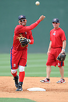 Second baseman Yoan Moncada (24) of the Greenville Drive works out with manager Darren Fenster watching at right, before a game against the Lexington Legends on Monday, May 18, 2015, at Fluor Field at the West End in Greenville, South Carolina. Moncada, a 19-year-old prospect from Cuba, made his professional debut tonight in the Red Sox organization. (Tom Priddy/Four Seam Images)