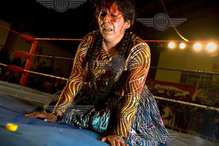 29 year old wrestler Martha La Altena (fighting name), Yenny Wilma Maraz (real name) after a fight at the Multifuncional building. Esperanza is a Cholita, a wrestler of native Aymara descent. When Cholitas fight they wear traditional costume. The blood on her face is believed to be fake, but the fighters insist that it is real. Yenny fights with the lucha libre (free wrestling) group Los Titanes del Ring. .....