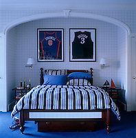 A pair of framed basketball jerseys hangs above the bed in this blue and white boy's bedroom