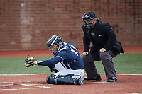 Wingate Bulldogs catcher Logan McNeely (18) frames a pitch as the home plate umpire looks on during the game against the Concord Mountain Lions at Ron Christopher Stadium on February 1, 2020 in Wingate, North Carolina. The Bulldogs defeated the Mountain Lions 8-0 in game one of a doubleheader. (Brian Westerholt/Four Seam Images)
