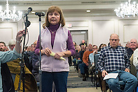 "Joanne Corrigan, of Plymouth, Mass., speaks at a public hearing regarding Pilgrim Station, a nuclear power plant run by Entergy, at Hotel 1620 in Plymouth, Massachusetts, USA, on Tues., Jan. 31, 2017. Corrigan opposed the continued operation of Pilgrim Station, citing safety concerns. ""The Commonwealth of Massachusetts loves it when the Red Sox are number 1. We love it when the Pats are number 1. But we don't love it when Pilgrim is number 1,"" she said during her comment, referring to area sports teams and an NRC rating of Pilgrim as the least safe nuclear plant in the US. An email from the NRC was leaked in December 2016 outlining problems with the ""safety culture"" at the plant and an ""overwhelmed"" staff. Area residents have been calling for the plant to be shut down. The green signs in the audience, reading ""Shut Pilgrim Now,"" are from a group of area residents calling for the plant's closure called Cape Downwinders."