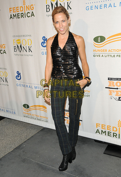 "SHERYL CROW .at The ""Rock a Little, Feed A Lot"" benefit concert to support the L.A. Regional Food Bank & Feeding America held at Club Nokia in Los Angeles, California, USA, September 29th 2009.        .full length black shiny halterneck top waistcoat grey gray trousers tartan plaid checked boots green blue zips bracelets hand in pocket .CAP/DVS.©Debbie VanStory/RockinExposures/Capital Pictures."