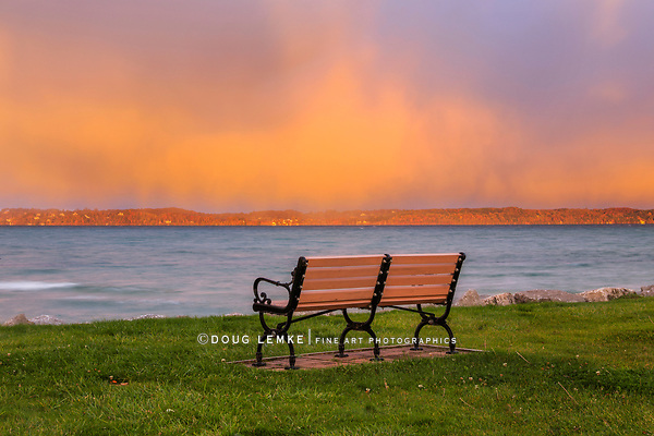 A solitary bench faces an orange sky over Traverse Bay early on a beautiful stormy morning at Elk Rapids, Michigan, USA