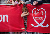 17 APR 2011 - LONDON, GBR - A young spectator peers between banners to watch the runners during the London Marathon .(PHOTO (C) NIGEL FARROW)