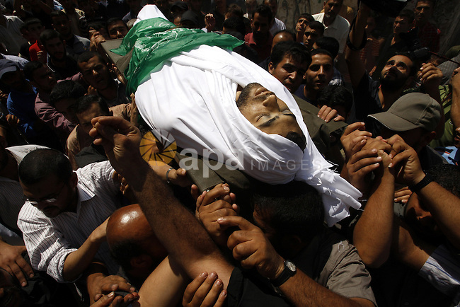 Palestinian mourners carry the body of Moussa Shtawe during his funeral in Gaza City on August 16, 2011 after he was killed and seven injured by overnight Israeli air strikes across the Gaza Strip, Palestinian medics said. The Israel Defence Forces (IDF) said the sites were targeted in response to the firing of a rocket from the Gaza Strip at the city of Beersheva. Photo by Mahmud Nassar