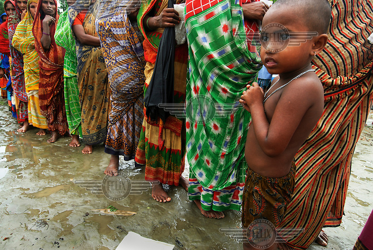 Women wait in the rain for Bangladesh Red Crescent Society aid packages after their village on the Kottimari Chor (a small river island) was submerged by severe flooding.