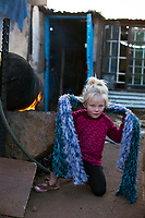 KRUGERSDORP, SOUTH AFRICA - JULY 18: A white Afrikaner girl tries to stay warm during a cold day outside her family shack in Munsieville township on July 18, 2018 in Krugersdorp a suburb in Johannesburg, South Africa. This black township, where South Africans and African immigrants live, now also has a separate section of poor white Afrikaners. They live side my side but they don't mix unless they have too. Many of the residents survive by begging at traffic lights and doing odd jobs. (Photo by Per-Anders Pettersson/Getty Images)
