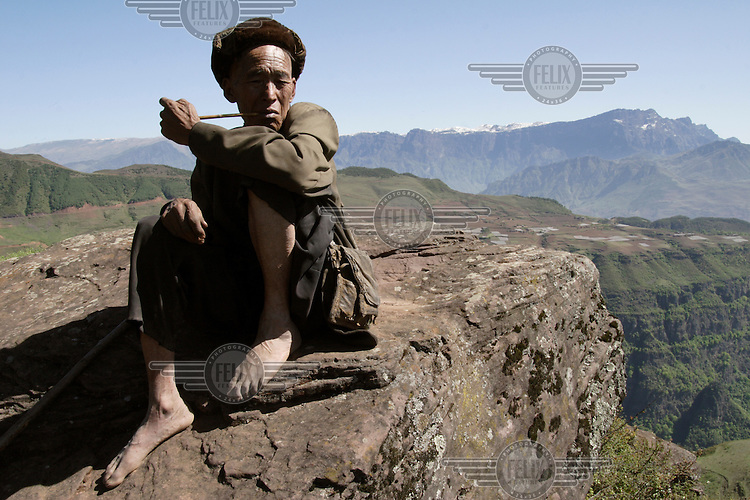 A barefooted Yi shepherd smokes his pipe.