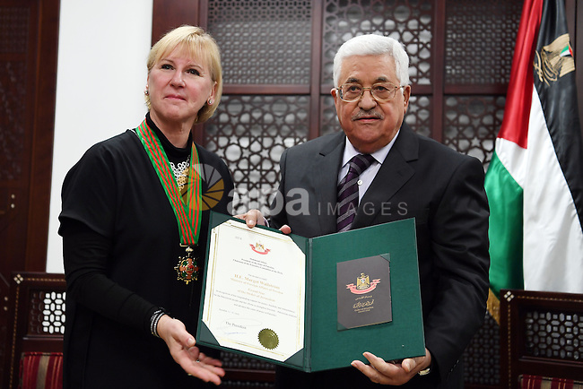 Palestinian president Mahmoud Abbas offers Swedish Foreign Minister Margot Wallström the Palestinian star during her visit to the West Bank city of Ramallah on December 15, 2016. Photo by Thaer Ganaim