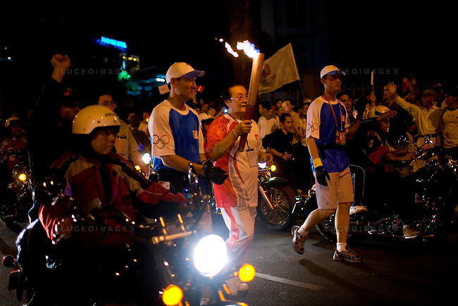 One of 60 torchbearers runs his leg of the Olympic torch relay down Pasteur Street heading north towards the Tan Son Nhat International Airport in Ho Chi Minh City, Vietnam. Pro-China demonstrators wave flags in support in the background...Thousands of people filled the streets of downtown District 1 in Ho Chi Minh City, Vietnam, to catch a glimpse of one of the 60 torchbearers complete the last leg of the Olympic flame's global journey outside China.  The Olympic torch relay began at the Opera House in the city center and conclude at a stadium near the Tan Son Nhat International Airport, covering a route of 10-13 kilometers. The Olympic flame will head to Hong Kong next. Photo taken Tuesday, April 29, 2008. Kevin German / kevin@kevingerman.com
